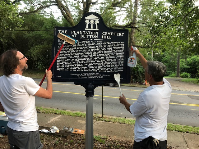 Mike Brezin and Mike Bannister cleaning the Sign