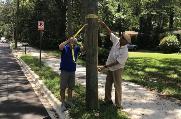 Mike Bannister and Mario Taylor removing the yellow caution tape on the newly completed Mitchell Avenue Sidewalk